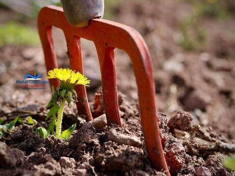 A resilient flower has sprouted next to a garden fork to show resilience; posted by https://www.market-connections.net
