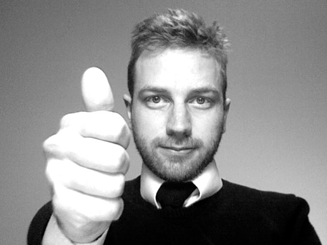 A man is holding his thumb up in an approval gesture in a black and white photo